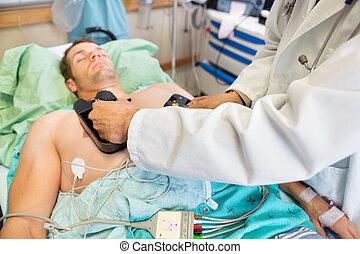 Doctor Defibrillating Patient In Emergency