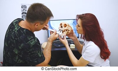 Doctor orthodontist checks a student how to treat teeth on the example of a human skull