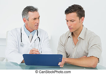Doctor discussing reports with patient at office