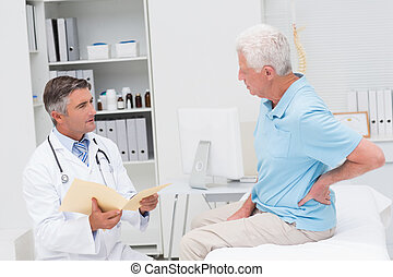 Doctor discussing reports with patient suffering from backache