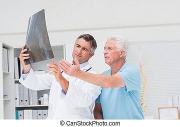 Doctor discussing with patient over x-ray - Male doctor...