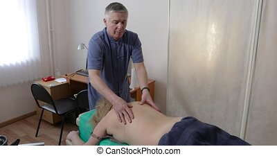 doctor does back massage of the woman