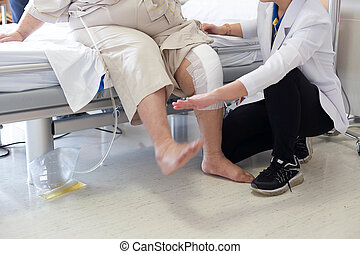 Doctor doing Physical therapy for Patient with a knee injury