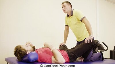 Doctor doing stretching exercises for disabled man - Doctor...