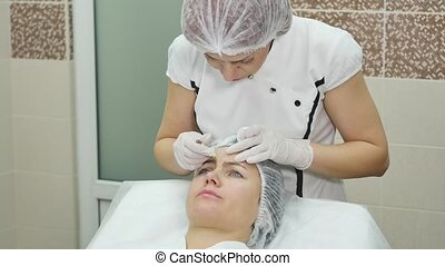 Doctor draw lines with marker on patient face for facial...
