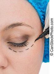 Doctor drawing around eye of woman