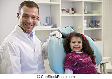 Doctor during visit of female child in dental clinic, portrait of young baby girl looking at camera and smiling