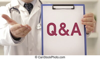 Doctor wearing a stethoscope pointing to Q&A sign, close up view on his hands and chest