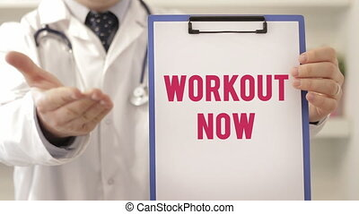 Doctor wearing a stethoscope pointing to workout preventative health care sign, close up view on his hands and chest