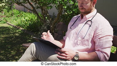 Caucasian doctor working at a retirement home, sitting on a bench in a park, checking examination results during a sunny day, during coronavirus covid19 pandemic.