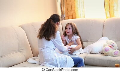 Doctor examines a little girl
