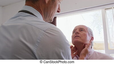 Caucasian male doctor working in his surgery at a retirement home, examining a senior Caucasian male patient, during coronavirus covid19 pandemic.