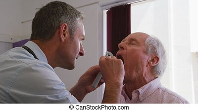 Caucasian male doctor working in his surgery at a retirement home, examining a senior Caucasian male patient with a laryngoscope, during coronavirus covid19 pandemic.