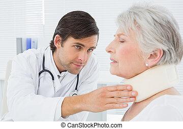 Doctor examining a senior patient's neck