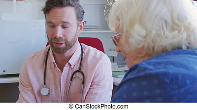 Caucasian male doctor wearing pink shirt and stethoscope, working in his surgery at a retirement home, talking with a senior Caucasian female patient, using a tablet, during coronavirus covid19 pandemic.