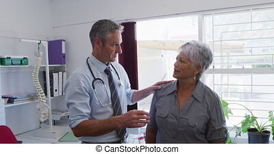 Caucasian male doctor working in his surgery at a retirement home, explaining treatment details to a senior mixed race female patient, during coronavirus covid19 pandemic.