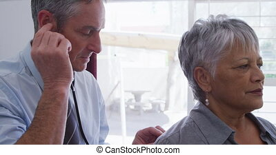 Caucasian male doctor working in his surgery at a retirement home, examining a senior mixed race female patient, using stethoscope, during coronavirus covid19 pandemic.