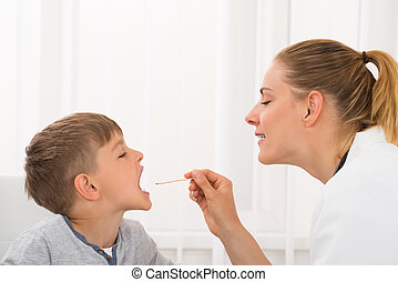 Doctor Examining Boy's Mouth
