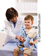 Doctor examining child - Senior female doctor examining ...