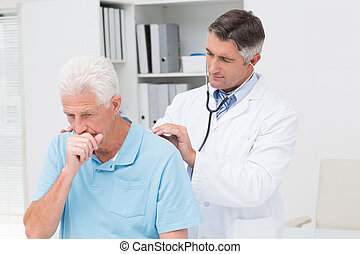 Doctor examining coughing senior patient