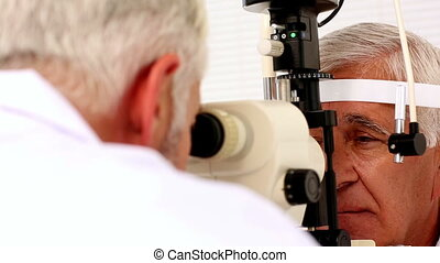 Doctor examining eyes of elderly patient in office at the...