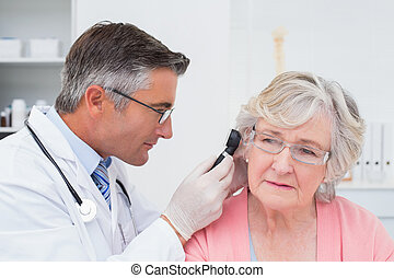 Doctor examining female patients ear with otoscope