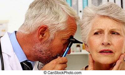 Doctor examining his patients ears