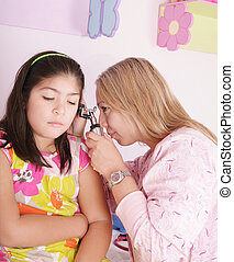 doctor examining little girl's ears with the otoscope
