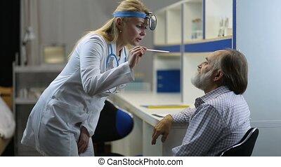 Doctor examining man's throat with tongue depressor -...