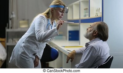Doctor examining man's throat with tongue depressor