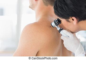 Doctor examining mole on back of man - Female doctor...