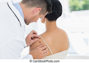 Male doctor examining mole on back of woman in hospital