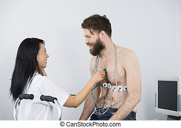 Doctor Examining Patient Cycling With Electrodes Attached On Bod