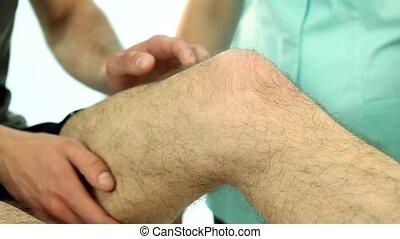 Doctor examining patient knee - Physiotherapist examining...