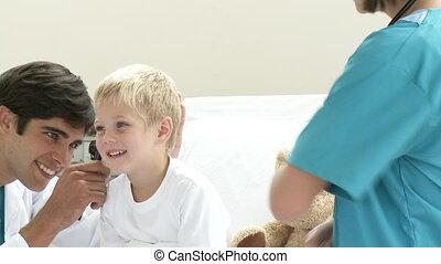 Doctor examining patient\\\'s ears wit