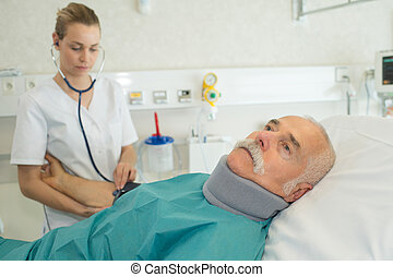 doctor examining senior patient on bed