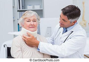 Doctor examining senior patient wearing neck brace