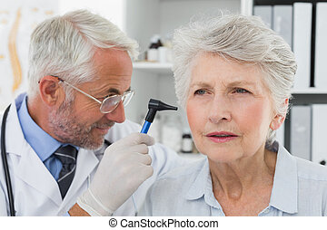 Doctor examining senior patient's ear - Close-up of a male...