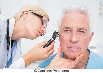 Doctor examining senior patients ear with otoscope