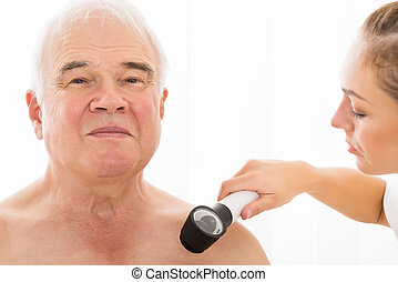 Doctor Examining Skin Of Patient With Dermatoscope