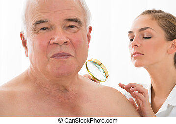 Doctor Examining Skin Of Patient With Magnifying Glass