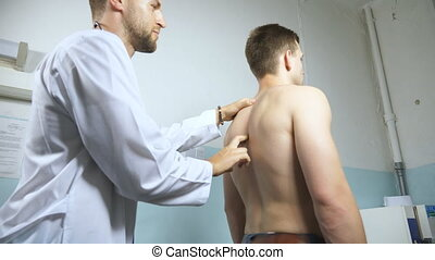 Doctor examining spine of young male patient. Medical worker...