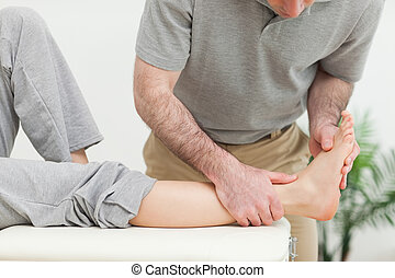 Doctor examining the foot of a woman while standing