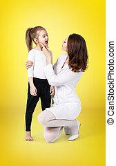 Doctor examining throat of little girl