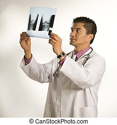 Doctor examining x-ray. - Asian American male doctor...