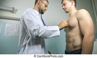 Doctor examining young male patient with stethoscope. Medic checking chest of guy in her office at the hospital. Medical worker listening heartbeat of athletic man. Close up