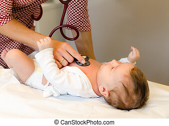 Doctor exams infant with stethoscope