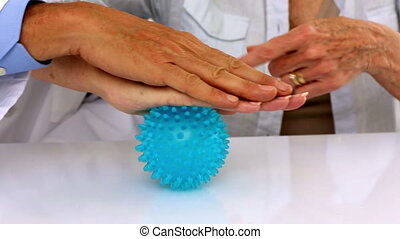 Doctor explaining a massage ball to patient in his office at...