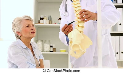 Doctor explaining a spine model to