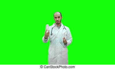 Doctor explaining difference between the pills on a Green Screen, Chroma Key.